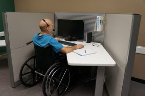 disabled man sitting in front of a computer