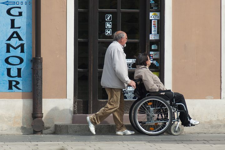 old woman in a wheelchair accompanied by a man